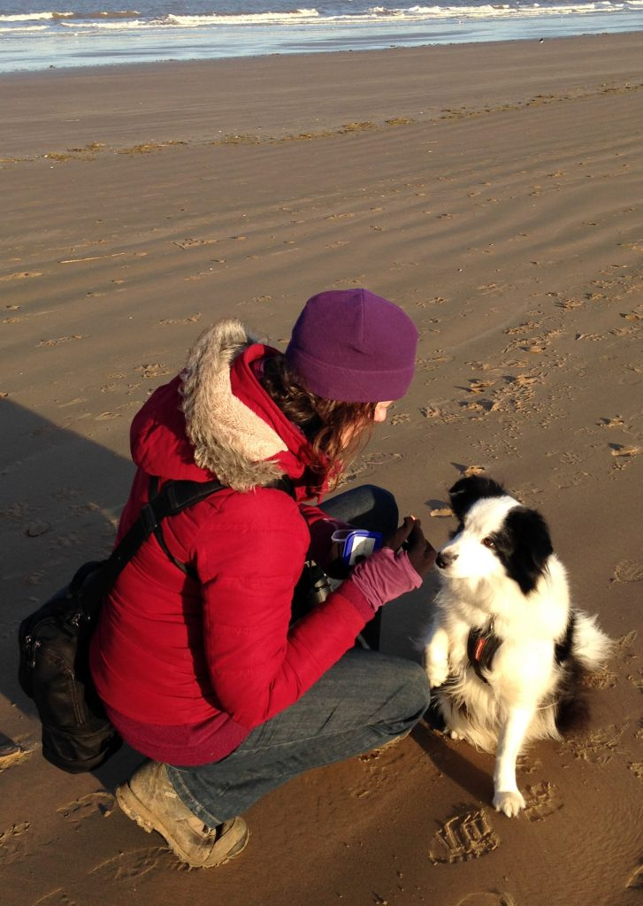 Photo of Ruth with her dog Amy on the beach.